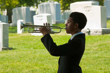 Arlington National Cemetery - 19 May 2012 - young man in silhouette playing Taps at the Taps 150 celebration, tombstones in background