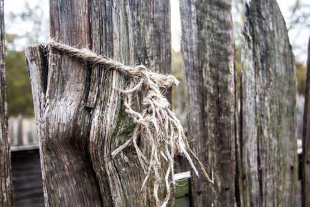 Tattered Rope Tied Around Fence Post photo