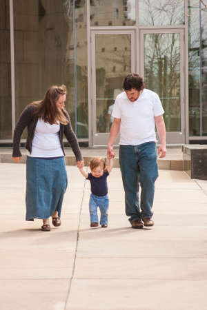 Toddler Walking down Sidewalk with Parents photo