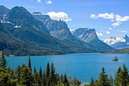 Isla Wild Goose en el Parque Nacional Glacier con picos montañosos en el fondo
