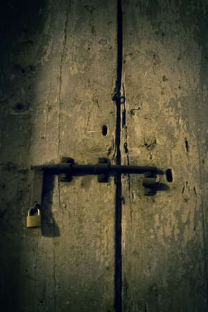 consumed: old wooden door with new padlock consumed Stock Photo
