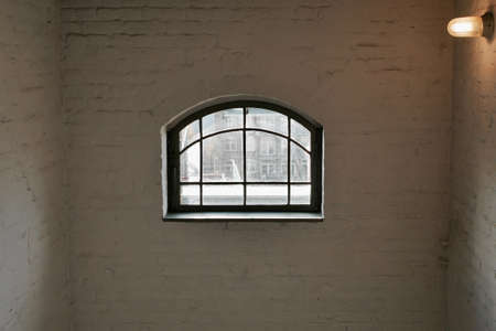 Arched window in a bare white painted brick room lit by a single globe on the wall with a view through to an urban square