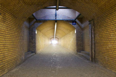 desolated: Empty arched brick tunnel or underpass with skylight and neon strip lighting receding into the distance towards bright sunlight at the end