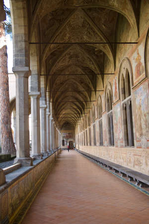 Long open air covered passageway with a historic Gothic vaulted ceiling , columns and arched windows receding into the distance with a lone figure just visible at the end