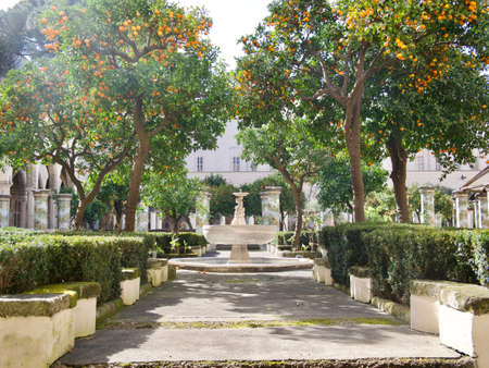 Pathway through a formal garden with fountain water feature under trees and a background of a classical historic building with colonnade of columns in front