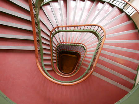 Spiral red staircase viewed from above with diminishing perspective