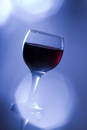 admonition: Glass of red wine in cold blue tone with flare.