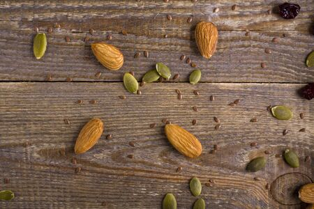 second meal: Grains, seeds, and the seeds scattered on a background of plank. almonds, pumpkin seeds, linseed and cranberry on wooden background.