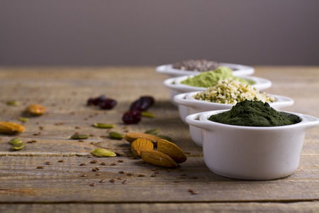 Superfood raw seeds and powder. Body building powders and health food on wooden background. Superfood served in small bowls.