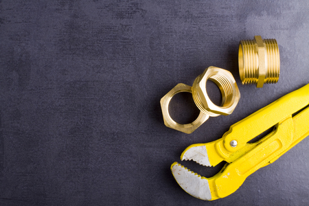fittings: Wrench and brass fittings on crude floor background.