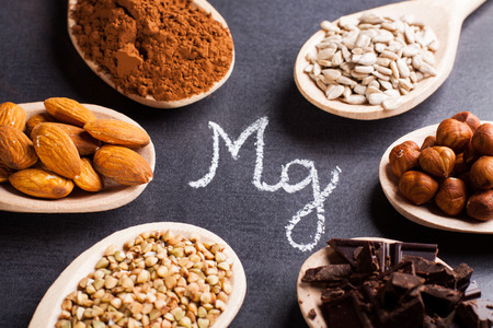 Products rich in magnesium on wooden spoons. 免版税图像
