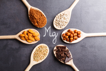 Products rich in magnesium on wooden spoons. 스톡 콘텐츠