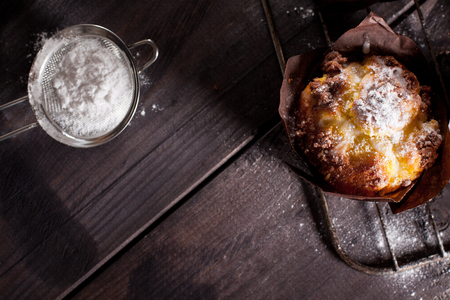 flourless chocolate cake: Muffins with white powdered sugar on wooden background.