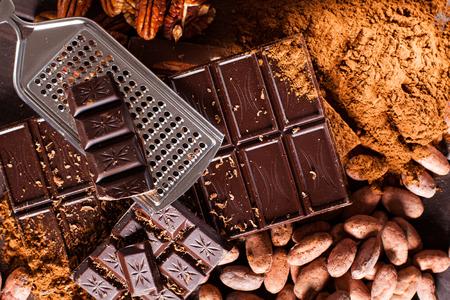 Schokoladenprodukte. Schokolade, Kakaobohnen, Kakao und Nüssen auf Holzuntergrund