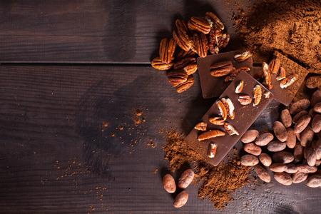 Chocoladeproducten. Chocolade, cacaobonen, cacao en noten op houten achtergrond Stockfoto