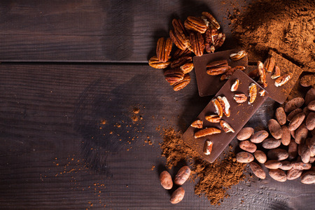 chocolate sweet: Chocolate products. Chocolate, cocoa beans, cocoa and nuts on wooden background Stock Photo