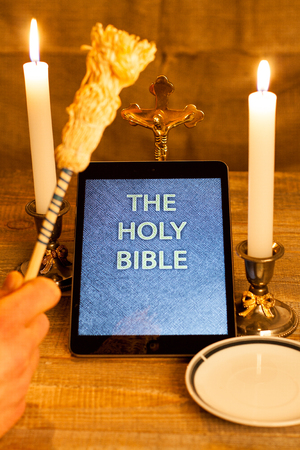 computerization: Digital  holy bible as a symbol of a new era. Scene from the cross, candles and sprinkler and hands folded in prayer