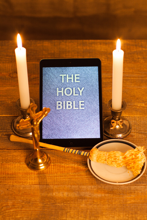 computerization: Digital  holy bible as a symbol of a new era. Scene from the cross, candles and sprinkler. Stock Photo