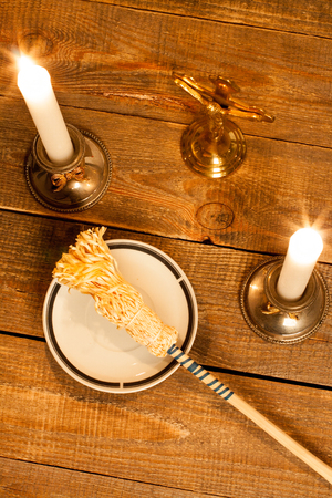priesthood: Gold cross with candles and sprinkler on wooden background.