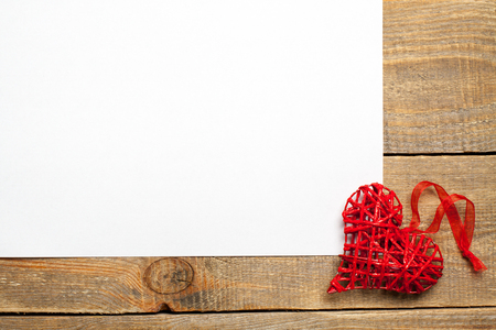 liaison: Blank sheet of paper on wooden background with heart.