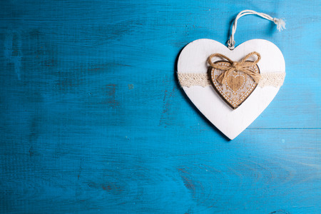 liaison: White heart on blue wooden background. Symbol of love in valentines day.