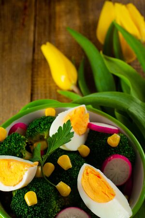 broccoli salad: Broccoli salad with tulip flowers on wooden background. Stock Photo