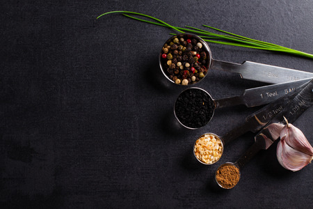 measuring spoons: Spices in stainless steel measuring spoons and fresh herbs with copy space.