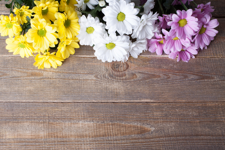 oxeye: Pink, white and yellow oxeye daisy flowers bouquet on wooden background.