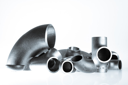 hardened: Steel welding fittings on group. Flanges, elbow, tees and plu on white space. Stock Photo