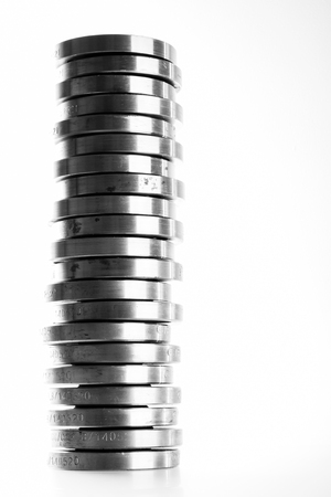 flanges: Stacked column of flat steel flanges isolated on white.