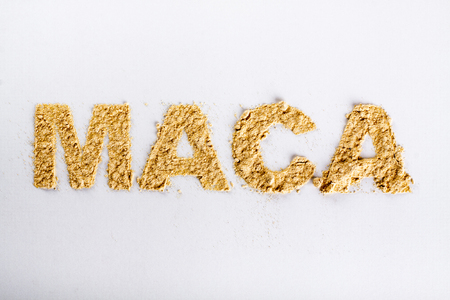 Word maca piled of maca root powder on a white background. Banco de Imagens