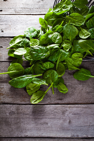 falling out: Baby spinach falling out of the metal basket on wooden background.