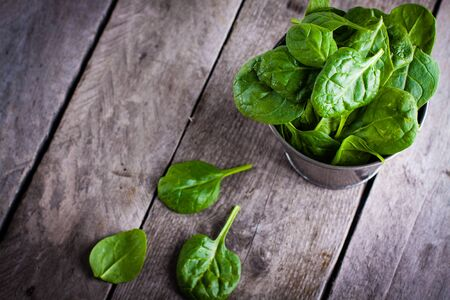baby spinach: Baby spinach in metal bucket on old wooden surface.