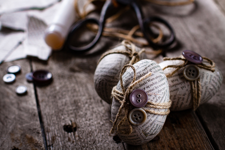 Easter eggs covered with scraps of newspaper wrapped in a jute twine with glued buttons. Handmade easter egg decoration. Stock Photo
