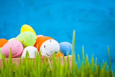 greenish blue: Basket of colorful Easter eggs in the grass on a blue background.