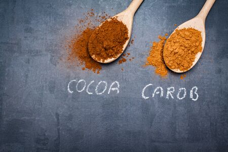 signed: Cocoa and carob powder on wooden spoons chalk signed on black stone background.