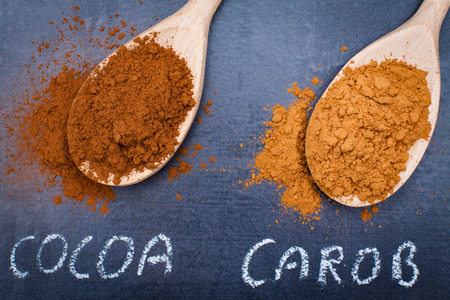 carob: Cocoa and carob powder on wooden spoons chalk signed on black stone background.
