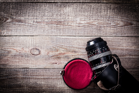 old macro: Old macro lens of 100 mm with a leather case on wooden table.