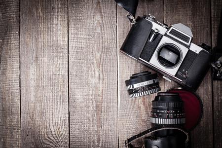 camara de cine: Cámara vieja de SLR con el caso de la lente y de cuero sobre la mesa de madera.