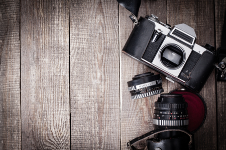 Old SLR camera with lens and leather case on wooden table. Stock Photo