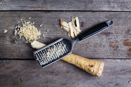 Grated horseradish root with grater on wooden gray table.