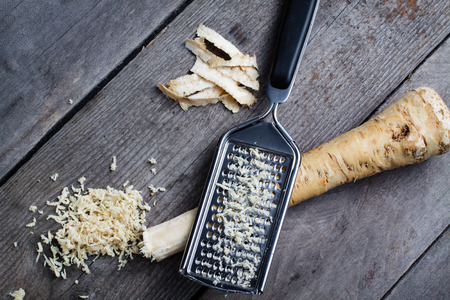 horseradish: Grated horseradish root with grater on wooden gray table.