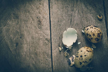 eggshell: Two quail eggs and broken eggshell on wooden old table. Stock Photo