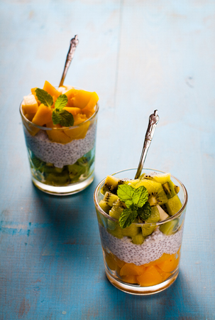 dietetic: Dietetic dessert in the form of a fresh fruit salad with kiwi and peach with chia seeds and yoghurt served in a glass.