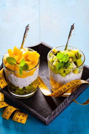 tailor tape: Dietetic dessert in the form of a fresh fruit salad with kiwi and peach with chia seeds and yoghurt served in a glass and lying tailor tape. Stock Photo