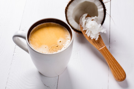 Bulletproof coffee, it's a coffee blended with butter or coconut oil. Wiev from above on coffee and coconut. Part of ketogenic diet, better choice before trainning. Stok Fotoğraf - 57666755