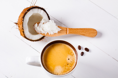 bullet proof: Bulletproof coffee, its a coffee blended with butter or coconut oil. Wiev from above on coffee and coconut. Part of ketogenic diet, better choice before trainning. Stock Photo