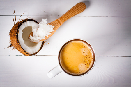 Bulletproof coffee, its a coffee blended with butter or coconut oil. Wiev from above on coffee and coconut. Part of ketogenic diet, better choice before trainning. Stock Photo