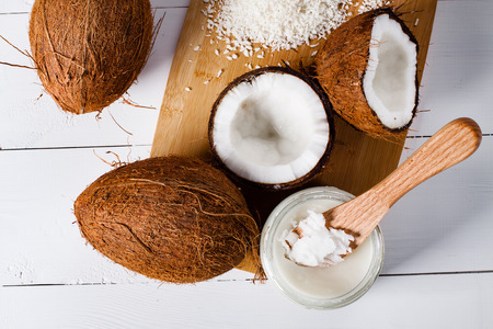 Whole and broken coconut with grated cocont flakes and coconut oil or butter. Stock Photo