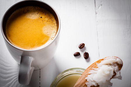 bulletproof: Bulletproof coffee, its a coffee blended with butter or coconut oil. Wiev from above on coffee and coconut. Part of ketogenic diet, better choice before trainning. Stock Photo